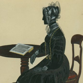 Painted and gilded silhouette of a lady seated at a table with an open book