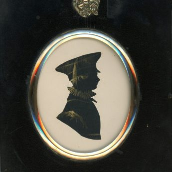 Cut and bronzed silhouette of a boy in a peaked cap