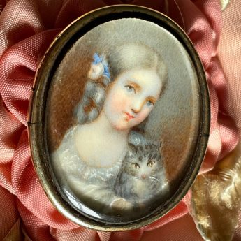 Miniature portrait of a child with a grey tabby kitten