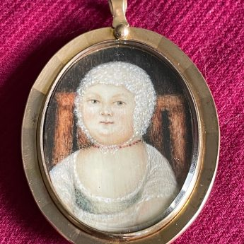 A cute miniature portrait of a baby on a wooden chair